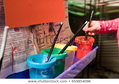A girl putting a paintbrush in a paint pot Stock photo © IS2