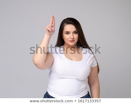 Emotional serious plus size model standing in studio holding glasses in her hand holding hair Stock photo © Traimak