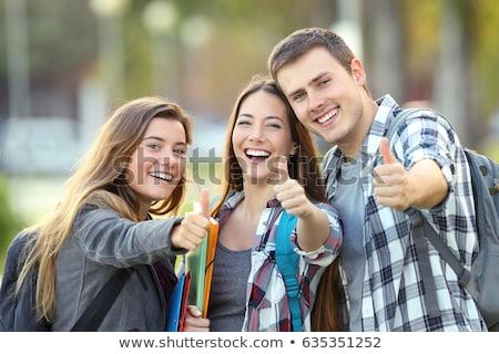 Drie grappig afgestudeerden poseren buitenshuis meisje Stockfoto © Lupen