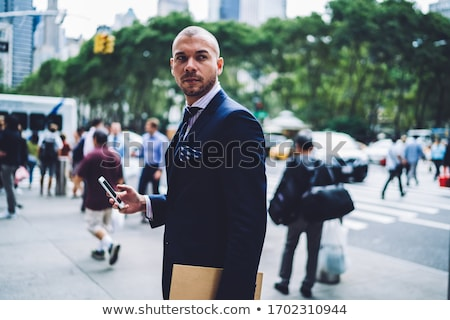 confident businessman in navy suit walking while looking to side Stock photo © feedough