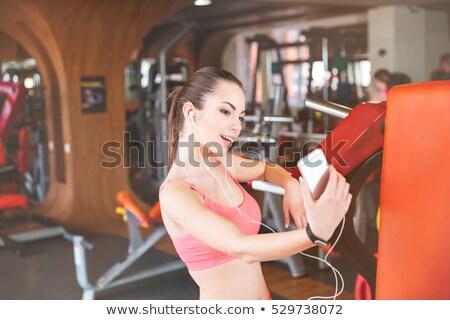 фотография улыбаясь спортивных женщину прослушивании Сток-фото © deandrobot