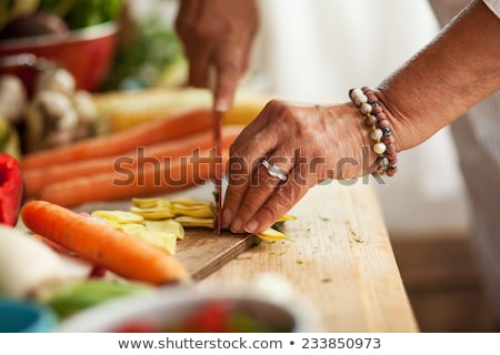 Woman's hands cut green leek on a wooden board on the kitchen table with various fresh vegetables. S Stock photo © artjazz