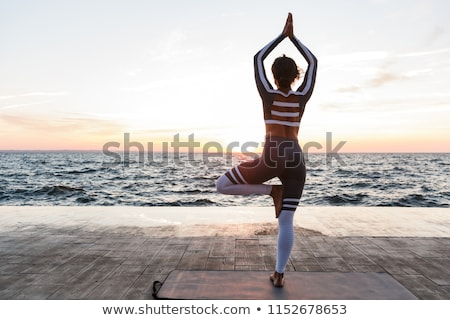 Amazing young sports woman make yoga exercises meditate outdoors on the beach. Stock photo © deandrobot