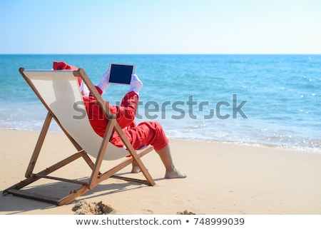 santa claus using a tablet on the beach stock photo © nito