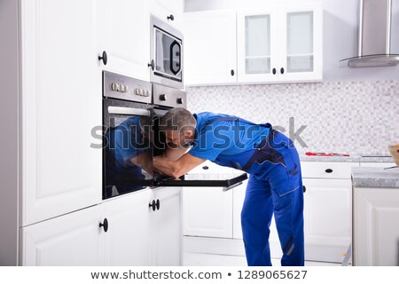 Repairman Fixing Kitchen Oven Stock photo © AndreyPopov