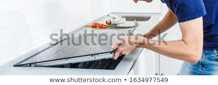 repairman fixing induction stove in the kitchen stock photo © andreypopov