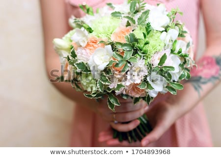 Beautiful bouquet of fresh roses in woman's hands with tatoo in a color of the year 2019 Living Cora Stock photo © artjazz