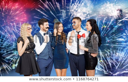 happy friends with party props over firework Stock photo © dolgachov