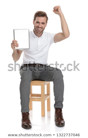 seated man reading good news on his tablet and celebrates  Stock photo © feedough