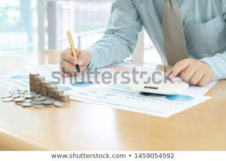 businessman using calculator with stacked coins arranged at offi Stock photo © Freedomz