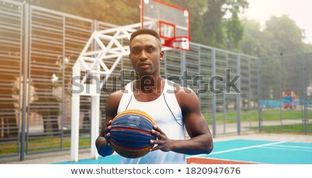 Young serious restful basketball player with ball sitting by fence of playground Stock photo © pressmaster