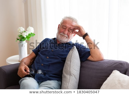 senior man  lying on sofa and thinking at home Stock photo © dolgachov