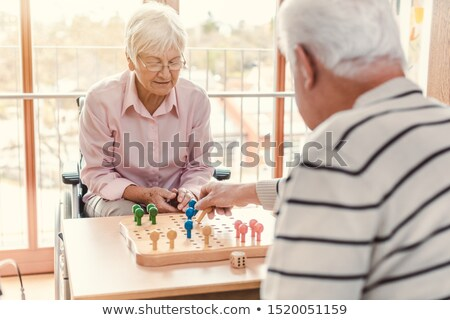 Nurse and senior in retirement home playing a board game Stock photo © Kzenon