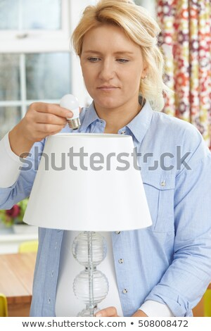 Woman Putting Low Energy LED Lightbulb Into Lamp At Home Stock photo © HighwayStarz