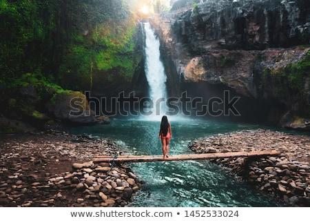 Man traveler on a waterfall background. Ecotourism concept Stock photo © galitskaya