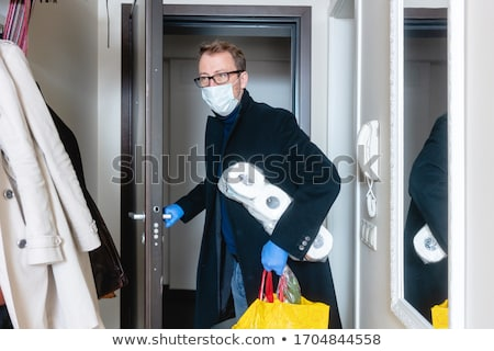 Man wearing medical mask coming home from shopping and hoarding Stock photo © Kzenon