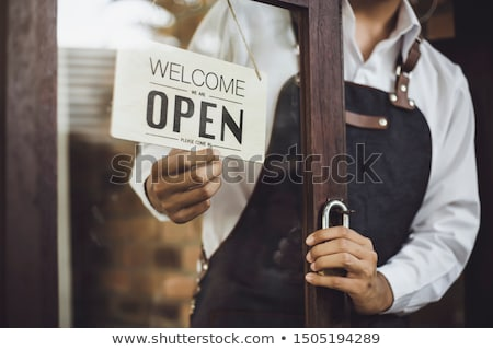 Business owner hanging an open sign at a glass door Stock photo © boggy