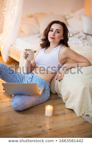 Optimistic lady with cup of hot beverage and candles sitting on  Stock photo © dashapetrenko