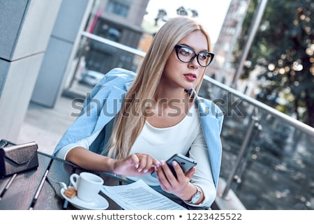 portrait of pretty young business woman sitting relaxed at outdo stock photo © hasloo