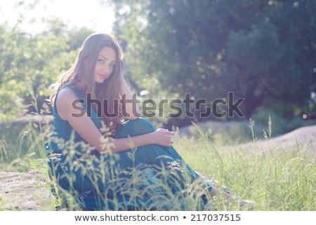 Mulher jovem rosa vestir sessão grama verde jovem Foto stock © rosipro