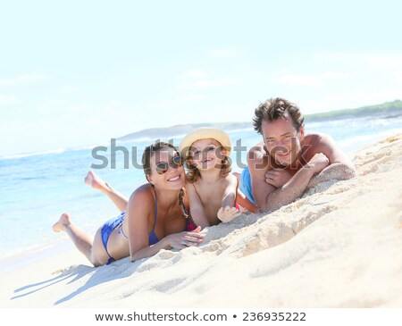 Happy family laying on the sand enjoying the ocean stock photo © Escander81