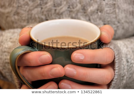 Two hands keeping warm, holding a hot cup of tea or coffee Stock photo © sarahdoow