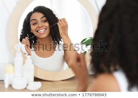 Stock photo: young lady brushing her teeth