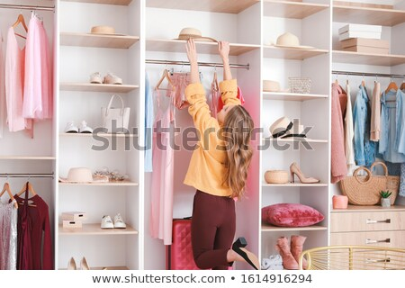 Young woman choosing what to wear in a closet Stock photo © deandrobot