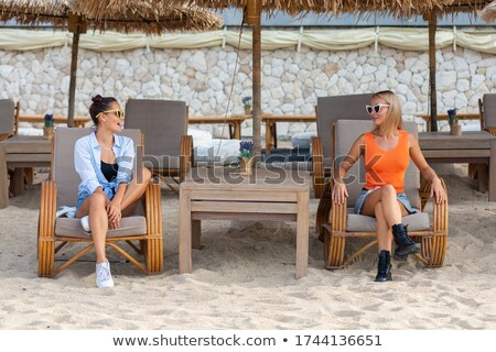 Side view of two young pretty friends sitting in cafe Stock photo © deandrobot