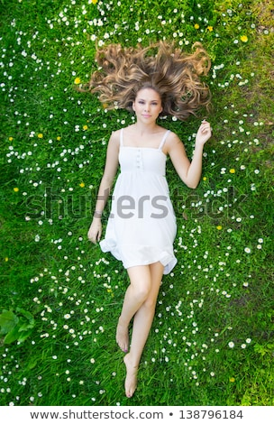 woman lying in grass with flowers stock photo © is2