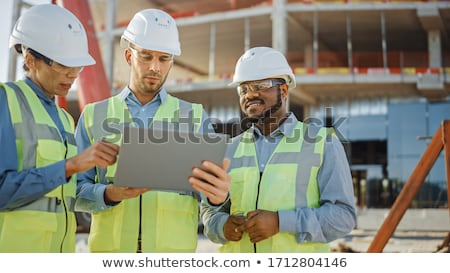 Woman Surveying plans at building site Stock photo © IS2
