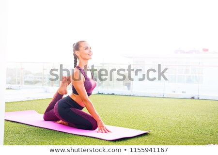 attractive woman wearing pink sportswear holding green yoga or f stock photo © dashapetrenko