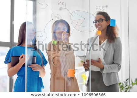 businesswomen with pie chart on office glass board stock photo © dolgachov