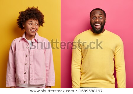 Image of amusing african american couple in colorful clothes hav Stock photo © deandrobot