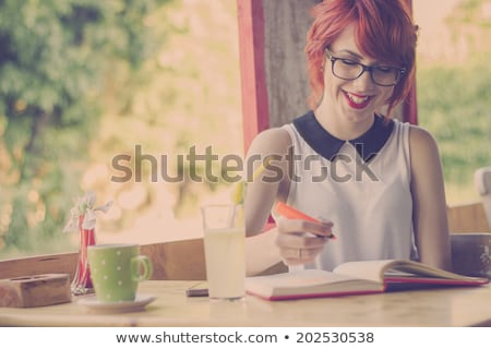 Focused red haired teenage girl studying at the table Stock photo © deandrobot
