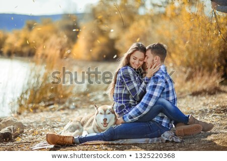 Stockfoto: A Young Couple Is Sitting By The Lake At Sunset With A Husky Breed Dog