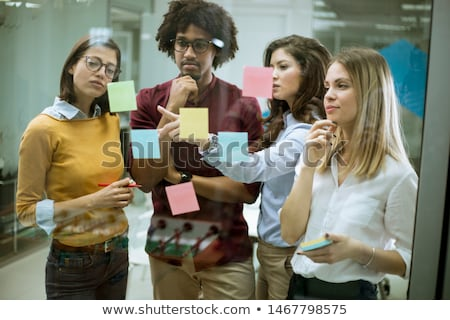Stock photo: Young business people discussing in front of glass wall using po