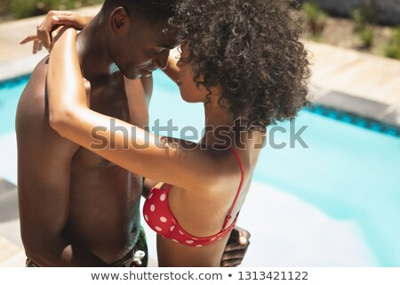 side view of young african american couple embracing at poolside in their backyard on a sunny day stock photo © wavebreak_media