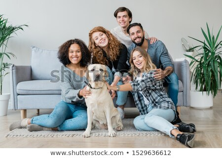 Cheerful young friendly companions and their cute pet relaxing at home Stock photo © pressmaster