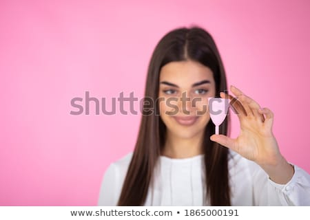 Young woman hands holding different types of feminine hygiene products - menstrual cup and tampons Stock photo © galitskaya