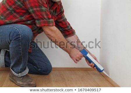 Home renovation, worker caulking batten with silicone Stock photo © simazoran