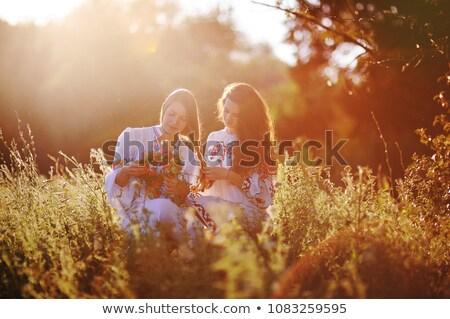 Girlsfriends weaving a braid outdoors Stock photo © pekour