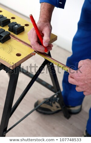 Stock photo: Plumber marking copper pipe
