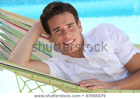 Man laid in hammock in front of swimming pool Stock photo © photography33