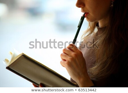 Cute woman thinking with pen and book Stock photo © wavebreak_media
