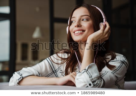 listens and smiles with headphones stock photo © filipw