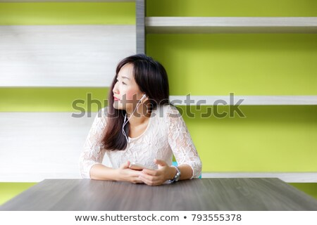 Gorgeous woman listening to music on her earphones Stock photo © dash