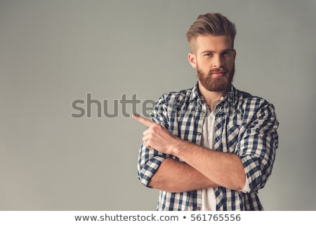 smiling casual man pointing away stock photo © stockyimages