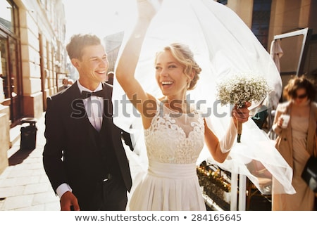 Smiling bride and groom with bouquets of flowers Stock photo © d13