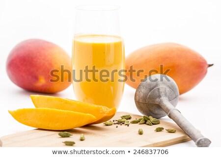 Glass Of Mango Lassi And Cut Fruit Pulp On White Stock photo © leowolfert